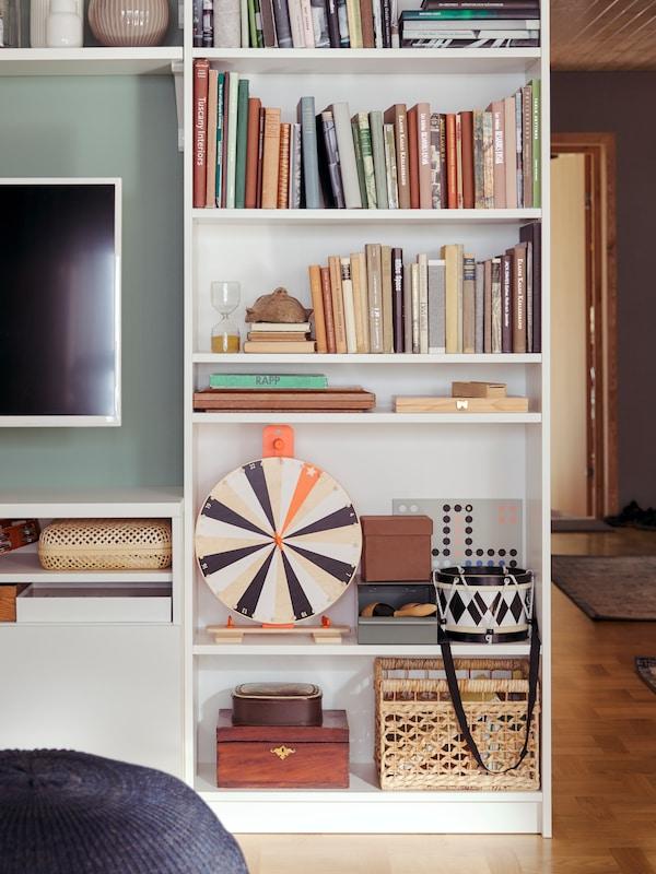 Uma poltrona ULRIKSBERG em rota, no canto de um quarto, à frente de uma estante HEMNES com livros e outros artigos.