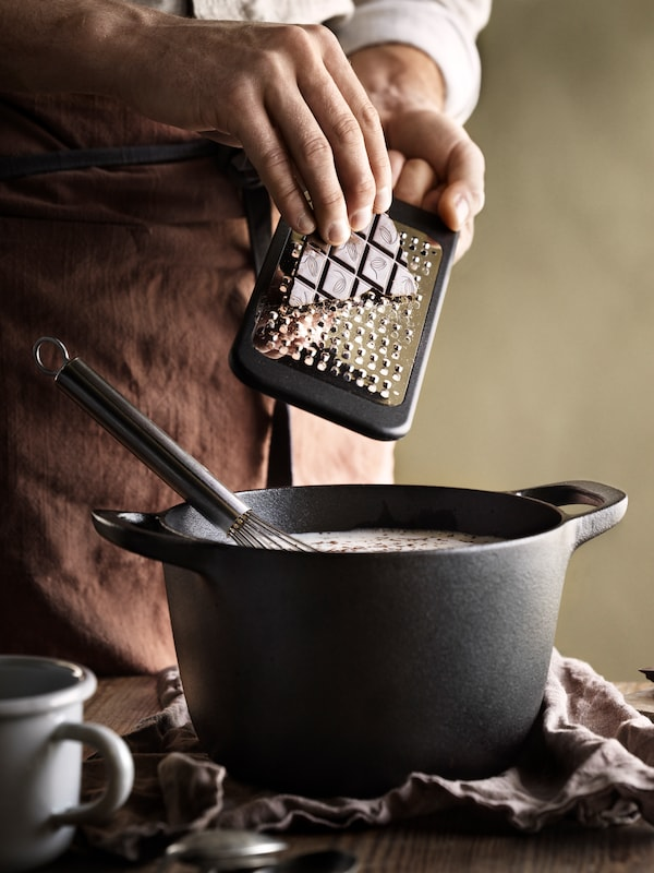 A person grating chocolate over a black cast iron pot of food on a table with a coffee cup.