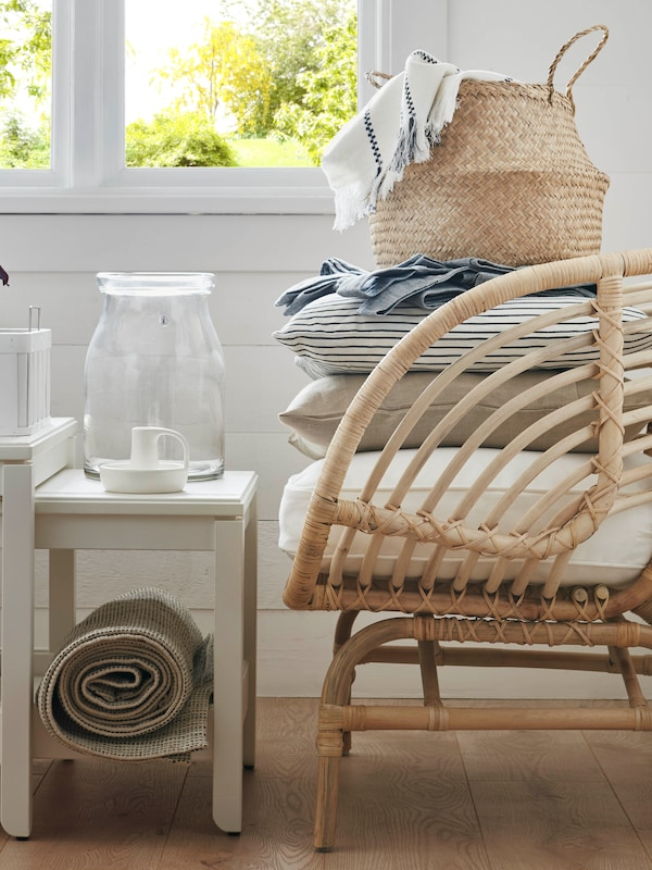 Un fauteuil en rotin sur lequel sont empilés des coussins, un jeté et un panier en jonc de mer.