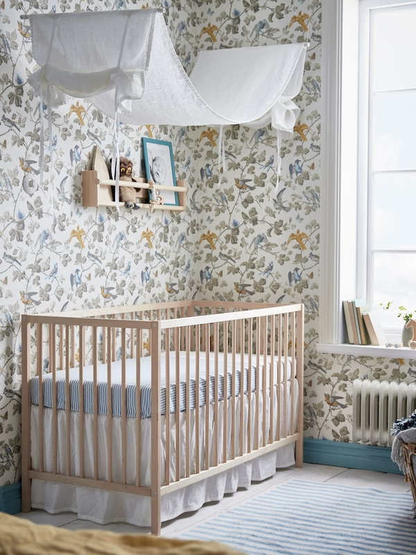 A SNIGLAR crib with blue GULSPARV sheets.