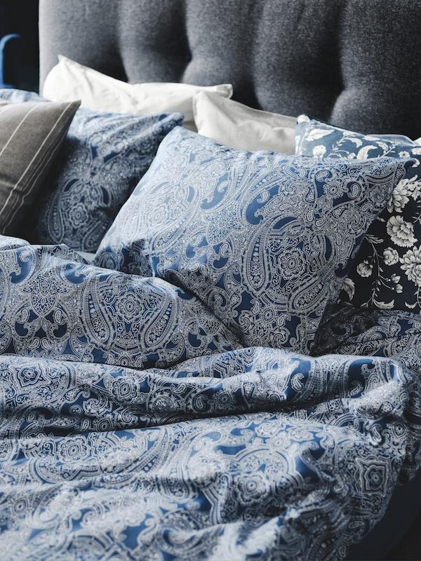 Ein graues, gepolstertes Bettgestell mit der JÄTTEVALLMO Bettwäsche und zwei Kopfkissen in weissem/dunkelblauem Paisley-Muster.
