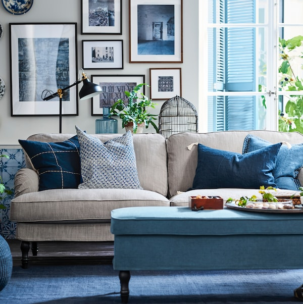 A beige sofa with cushions in blue and grey, a wall behind with lots of pictures in picture frames, footstool in front.