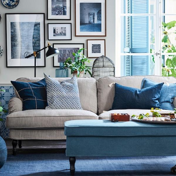 Ein Sofa in Beige mit Kissen in Blau und Grau steht vor einer Wand mit vielen Bildern in Bilderrahmen. Vor dem Sofa befindet sich ein Hocker.