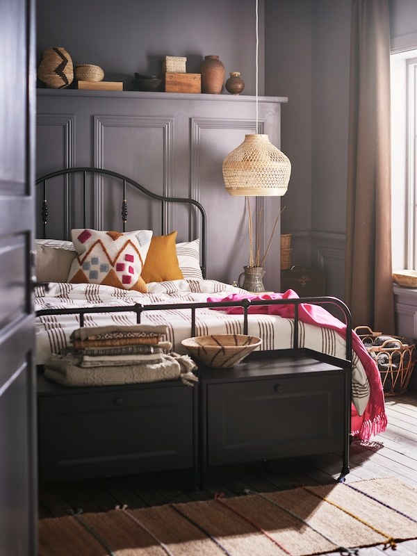 Két fekete tárolós pad és fekete ágykeretes ágy csíkos ágyneművel és egy sokszínű BRUNSTARR párnával.