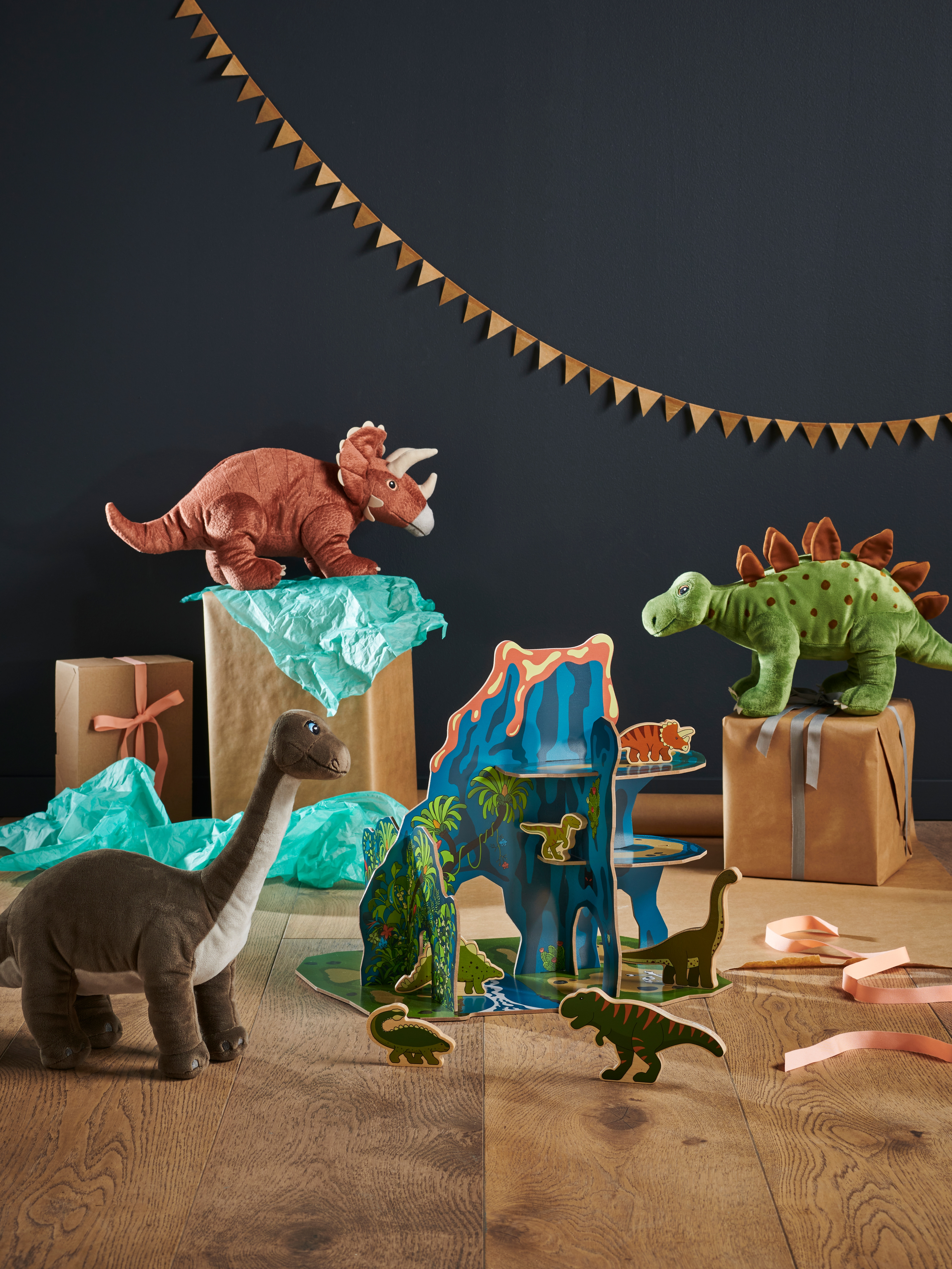 JÄTTELIK cardboard volcano and soft toy dinosaurs surrounding wrapped boxes and tissue paper with bunting in background.