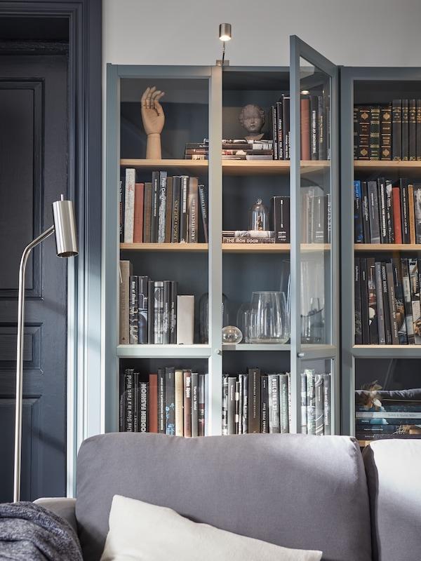 Harmaanturkoosi BILLY-kirjahylly joka on täynnä kirjoja. Kaapin päällä on URSHULT-kaappivalaisin. Kaapin edessä on harmaa VIMLE-sohva jolla on valkoinen VIGDIS-koristetyyny.