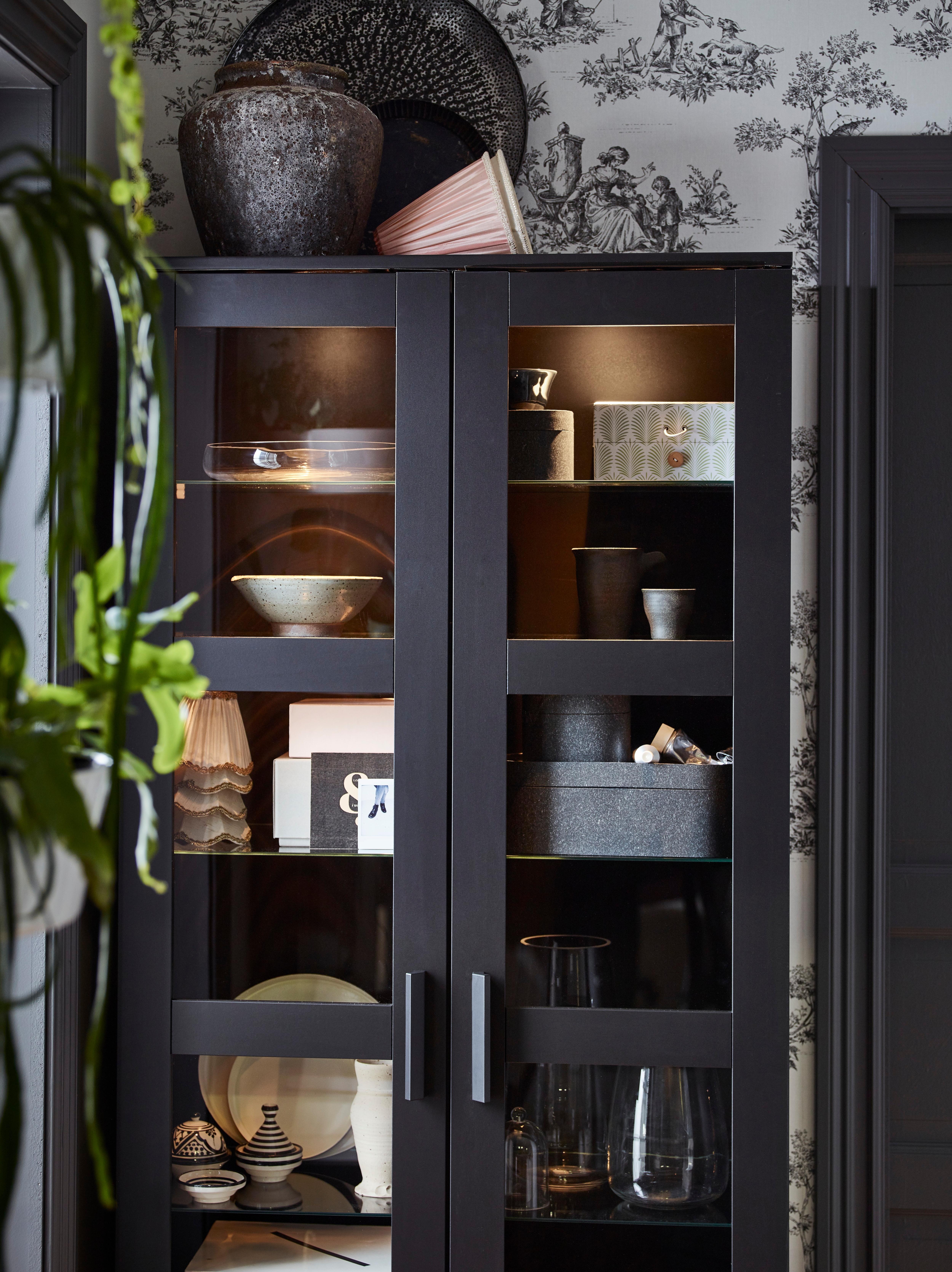Crna BRIMNES vitrina sa staklenim policama osvjetljava dekor poput kutija, zdjela i visokih vazi.