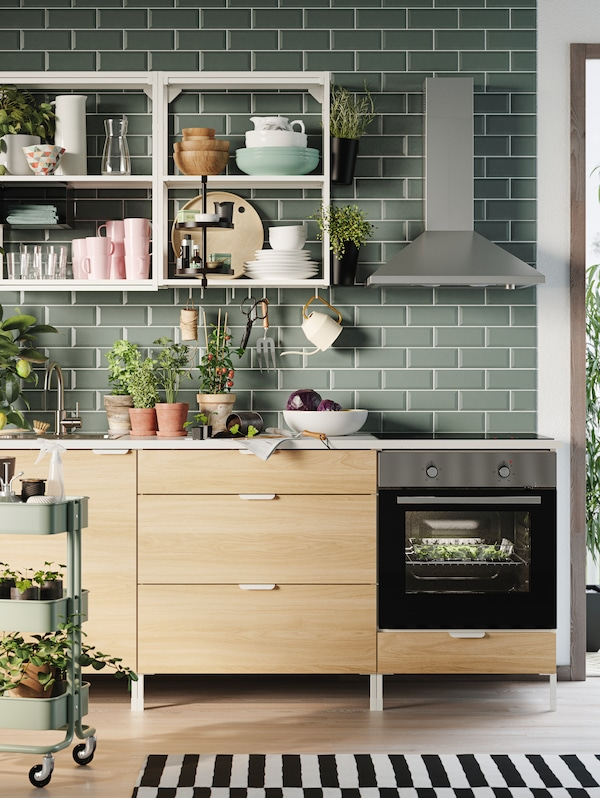 In a pale green-tiled kitchen, an oak ENHET kitchen combination with white open shelving displays tableware and plants.