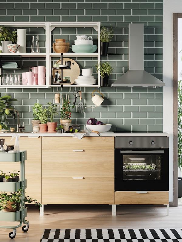In una cucina con piastrelle verde chiaro, una combinazione ENHET in rovere con scaffali a giorno bianchi dove sono riposti articoli per la tavola e piante.