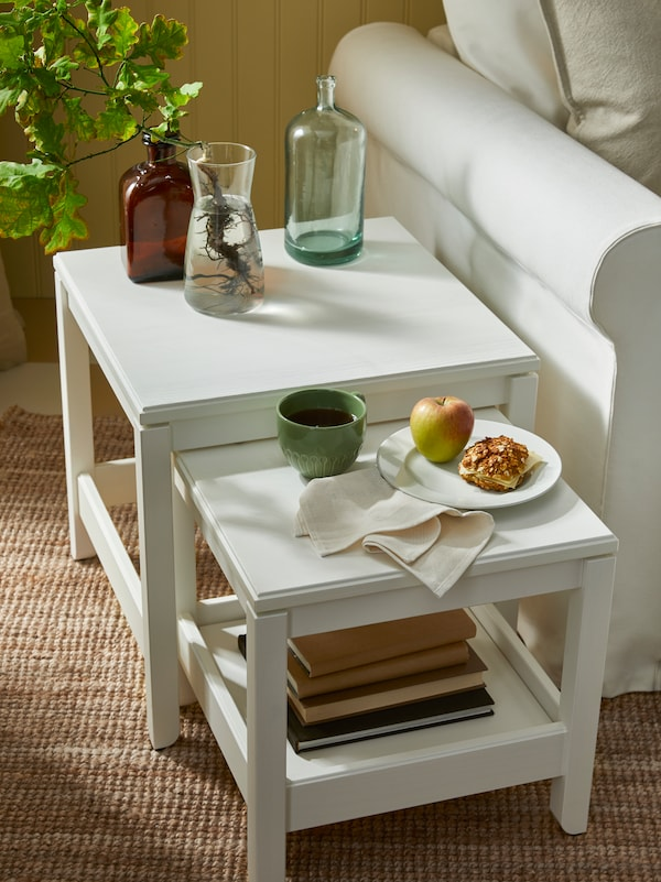 Coffee tables in white, one holding bottles and a glass vase with a green plant, the other holding a cup and a plate.
