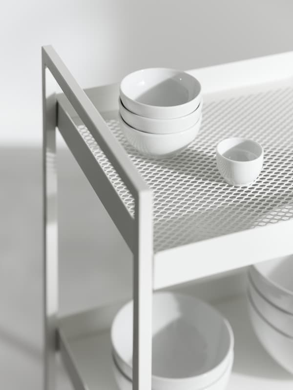 The top of a NISSAFORS trolley with white dinnerware on the shelves, showing the mesh detail on the top shelf.