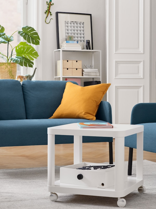 A blue GLOSTAD sofa with two cushions standing on a rug in a white room in front of a white table.