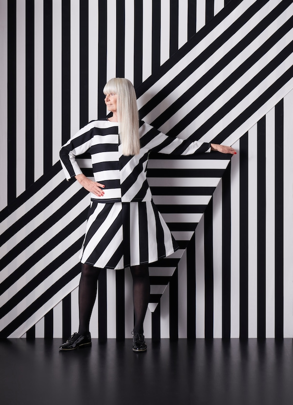 A woman wearing a dress made from black and white striped SOFIA fabric stands in front of a wall covered in the same fabric.