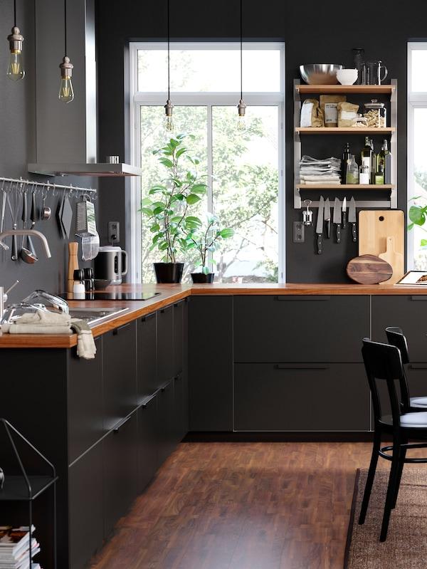 Кухня Kungsbacka з білими й чорно-синіми дверцятами, двома NORRÅKER НОРРОКЕР лавками і столом з берези на темно-синьому килимі.