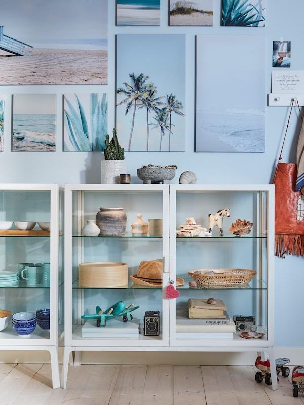 To hvide vitrineskabe med pyntegenstande, blå vægge og billeder med strandmotiver på væggen.