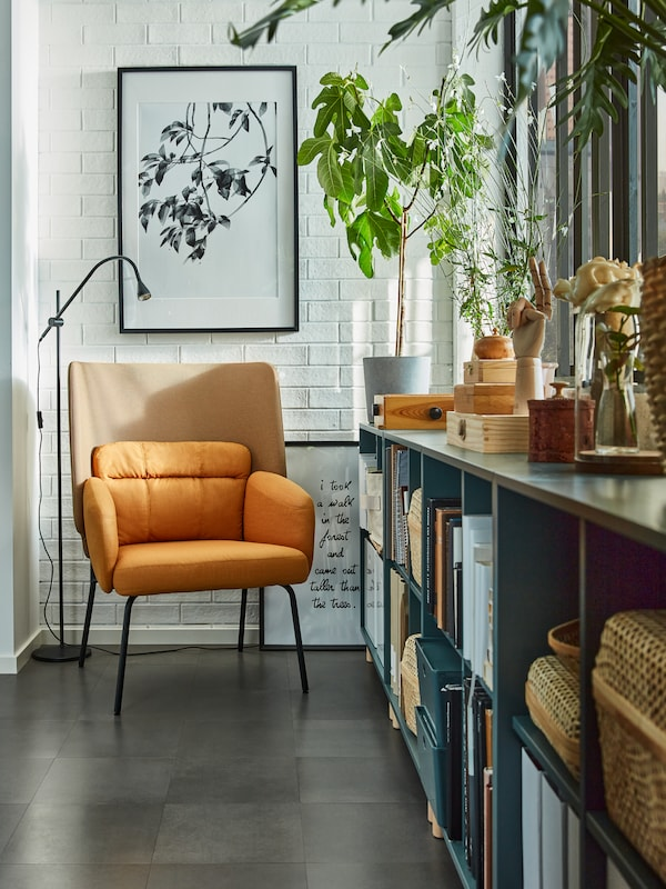 A reading nook with a yellow armchair, a black reading lamp, grey-turquoise cabinets by the window with books and boxes.