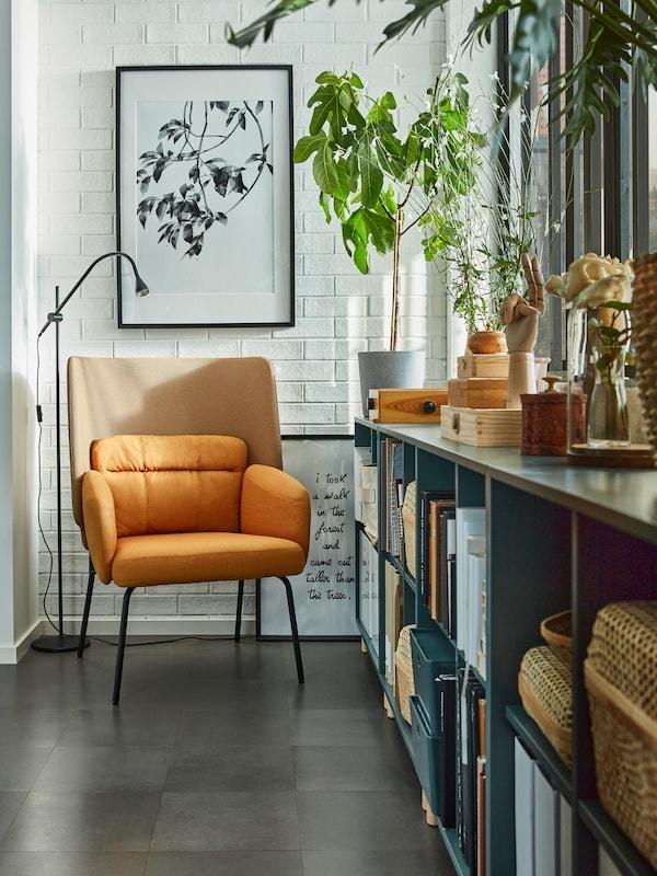 Recuncho de lectura cunha cadeira de brazos amarela, unha lámpada de lectura negra, armarios gris-turquesa xunto a unha ventá con libros e caixas.