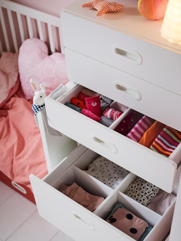 Cómoda STUVA/FRITIDS branca con caixóns abertos nos que hai caixas RASSLA con compartimentos para clasificar roupa de cores.