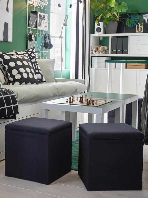 Un salon dans les tons verts où se trouvent des tissus à motifs. Un repose-pieds avec rangement BOSNAS noir est placé à côté de la table basse.