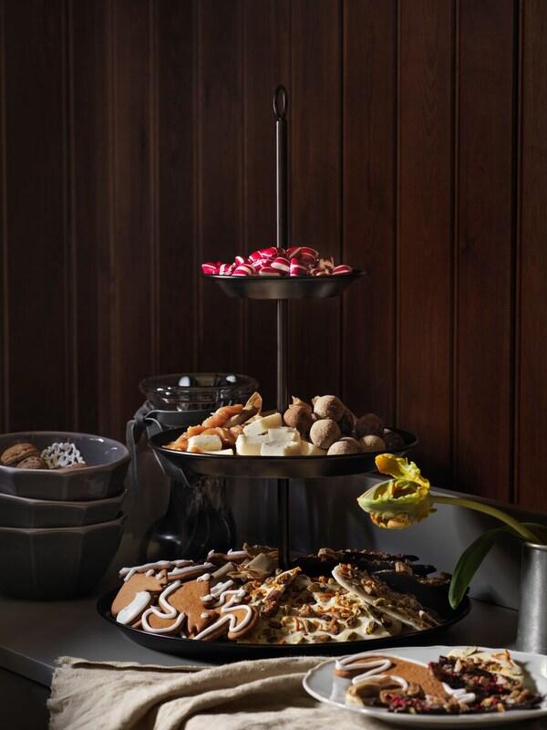 Eine INBRINGANDE Etagere ist mit Gebäck und Snacks gefüllt und steht auf einem Sideboard bereit für die Party.