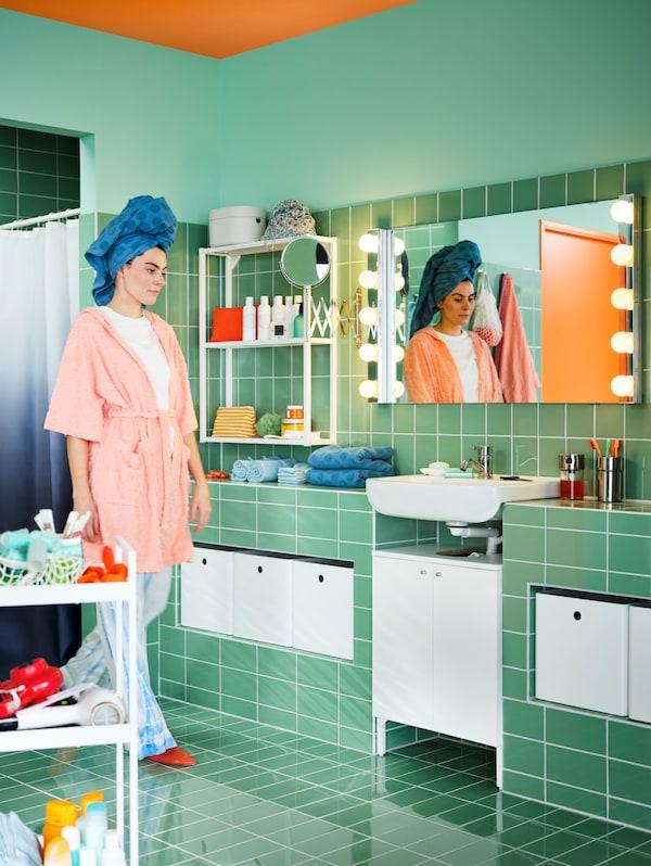Ein grün gefliestes Badezimmer mit einem weißen BJÖRKÅN Waschbecken und einem NYSJÖN Waschbeckenschrank mit einer Tür. Daneben steht eine Frau im Schlafanzug.