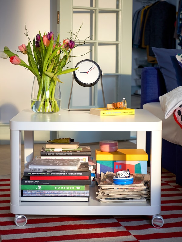 TINGBY white side table on castors, with lots of books on the lower level and with a vase of flowers and a clock on top.