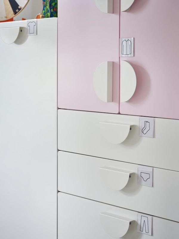 Suporturile pentru etichete HÄNGIG cu ilustrații de haine sunt fixate pe depozitul SMÅSTAD alb și roz cu mânere BEGRIPA.