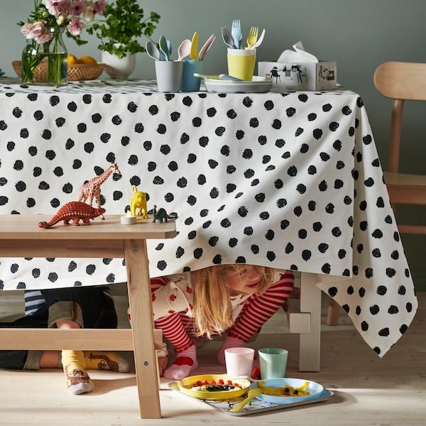 Seorang kanak-kanak mengintai keluar dari bawah meja yang ditutupi dengan alas meja yang dibuat daripada fabrik SKÄGGÖRT berwarna hitam dan putih.