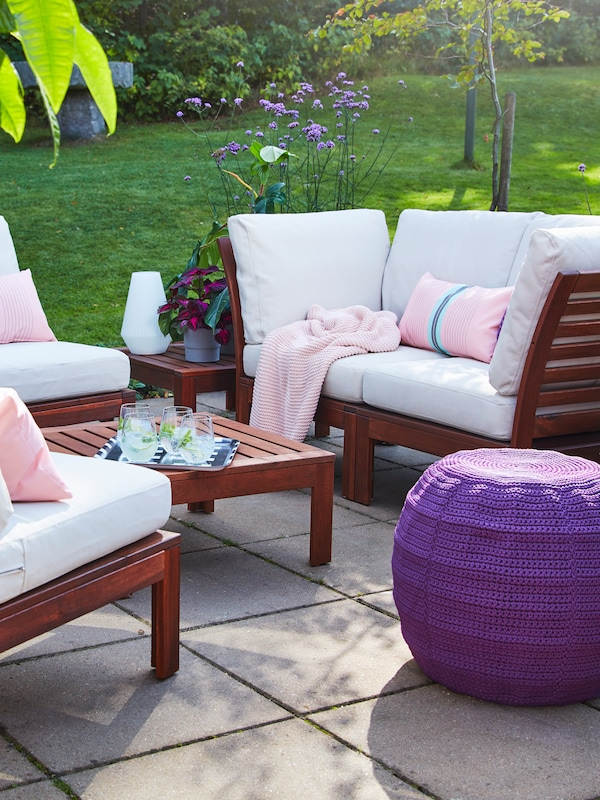 A wooden coffee table outside, with wooden sofa and armchairs, white upholstery, pink cushions and throw, purple pouffe.