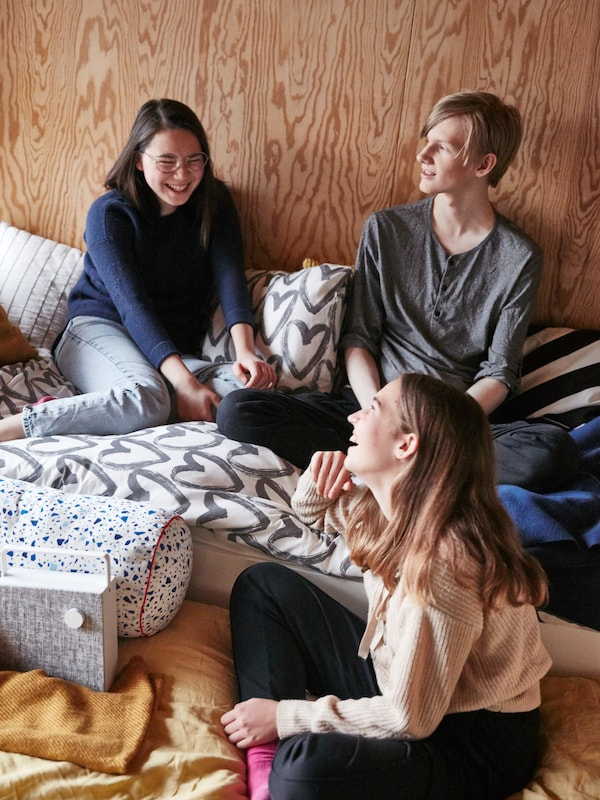 A teen room with a white SLÄKT bed frame, cushions and bed linen in different colors, and three friends hanging out.