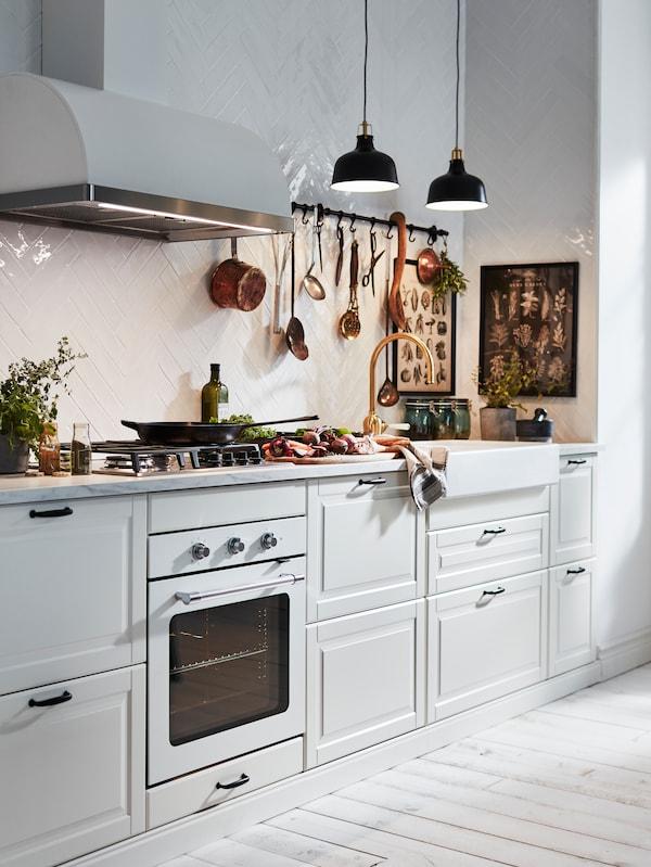 Krem BODBYN kuhinja s namirnicama na radnoj ploči, tavom na MATMÄSSIG plinskom kuhalištu i dvije crne RANARP visilice.