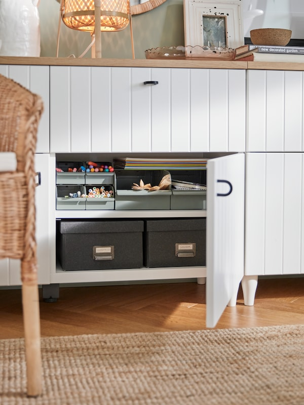 A white cabinet with black handles, pens and paper in grey-green boxes and dark grey boxes with lids.