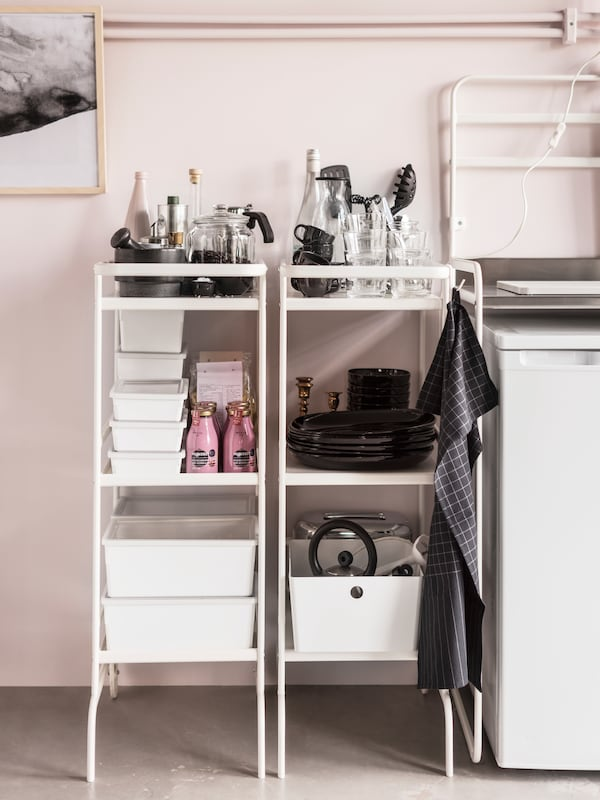 Two white trolleys stand against a pink wall in a kitchen storing kitchen supplies and tableware.