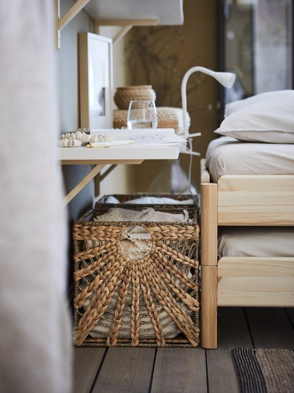 Ein Regal als Ablagetisch, zwei LUSTIGKURRE Körbe aus Wasserhyazinthe/Seegras und der Kopfteil eines Bettes.