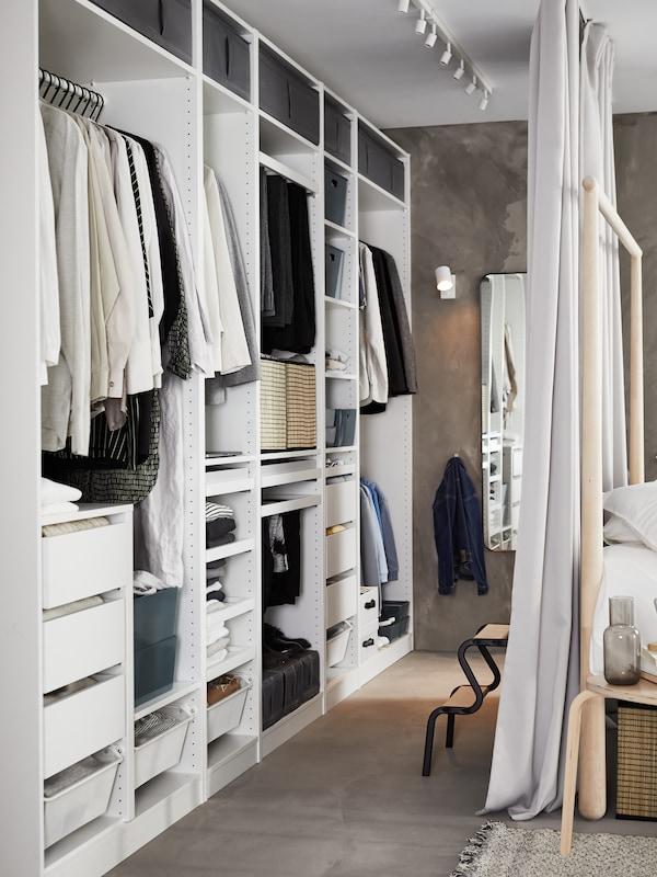 PAX gardróbszekrény rengeteg tárolóhellyel, a belsejében ruhaneműk és különféle dobozok, és egy GJÖRA ágy széle látható.