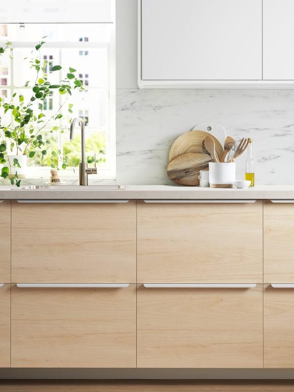 Kuhinja s drvenim frontama, bijelim radnim pločama i bijelom zidnom oblogom s efektom mramora. Pokraj sudopera i prozora nalazi se biljka.