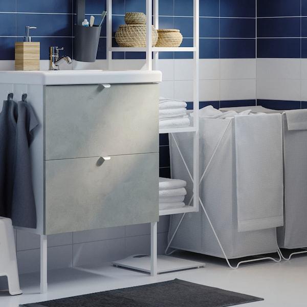 Bad med hvitt servantskap med to grå skuffer. Ved siden av står det en hvit, åpen veggstamme og to skittentøykurver.