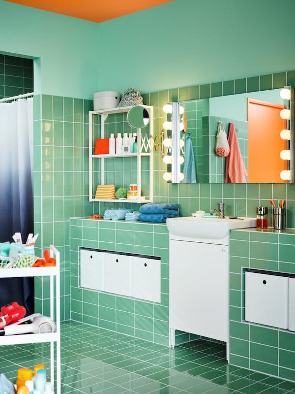 Badrum med rektangulär LETTAN spegel med vägglampor ovanför ett vitt BJÖRKÅN tvättställ och ett vitt NYSJÖN tvättställsskåp.