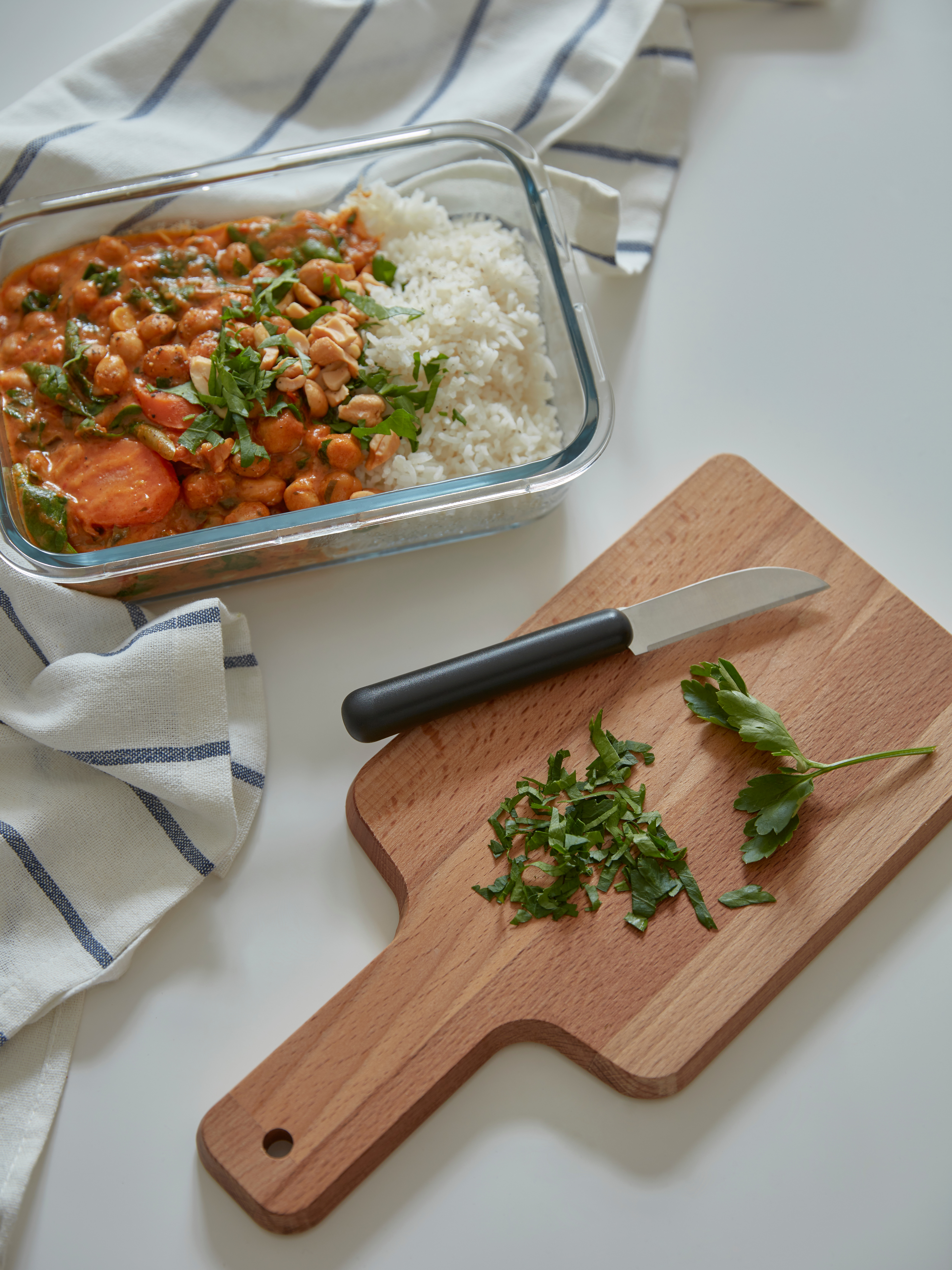A PROPPMÄTT chopping board in beech with some chopped herbs on it along with a knife, and a glass dish of food on the table.
