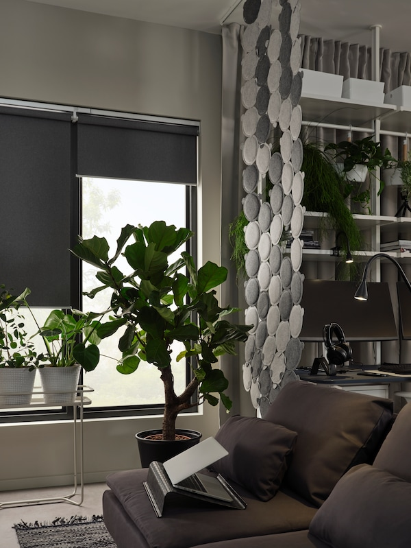 Un rideau étroit fait de panneaux acoustiques ODDLAUG sépare un bureau à domicile d'une zone avec un canapé SÖDERHAMN.