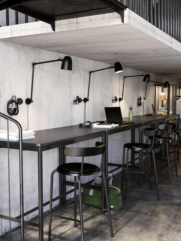 Spazio di co-working con soffitto basso e una fila di postazioni lungo una parete, ciascuna con una lampada da lavoro/parete SKURUP e uno sgabello bar YNGVAR.