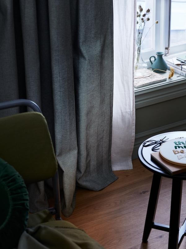 Des rideaux assombrissants TIBAST vert foncé sont installés par-dessus des rideaux HANNALILL plus légers à une fenêtre. Des livres décorent le rebord de la fenêtre.