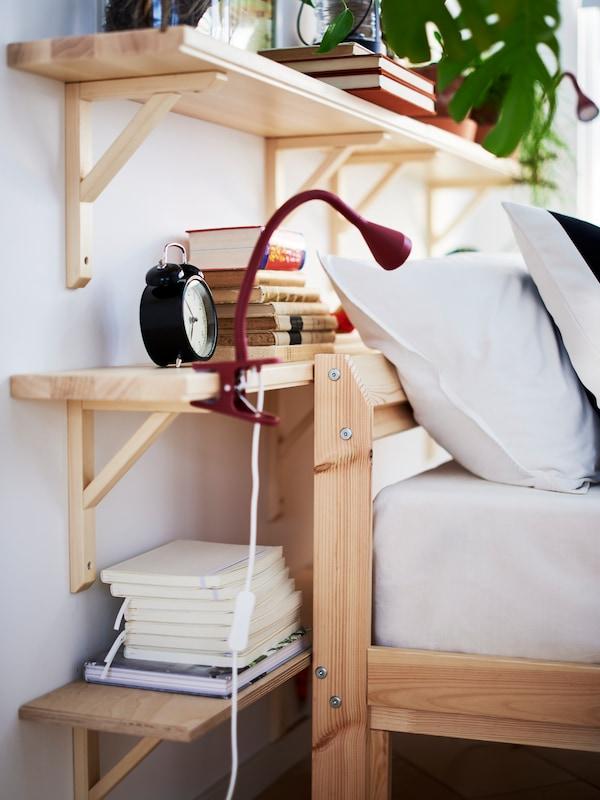 Dark red, NÄVLINGE LED clamp spotlight on an aspen, TRANHULT/SANDSHULT wall shelf at the head of a pine, TARVA bed frame.
