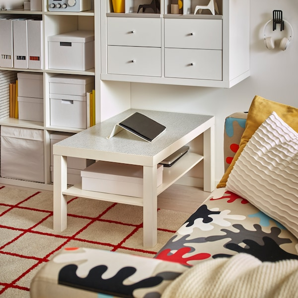 A LACK side table in white with a tablet on a tablet holder resting atop it, in the middle of a living room.