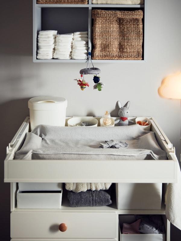 Une housse SKÖTSAM grise pour prendre soin du bébé est placée sur une table à langer SMÅSTAD blanche entourée de boîtes et de jouets.