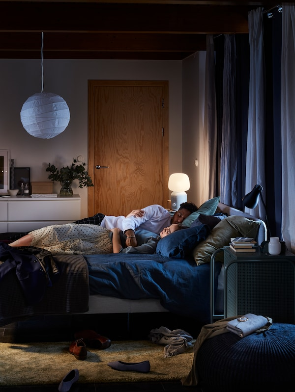 Una pareja tumbada en una cama con ropa de cama PUDERVIVA en azul oscuro. Detrás de la cama, hay una lámpara de mesa SYMFONISK con altavoz wifi.