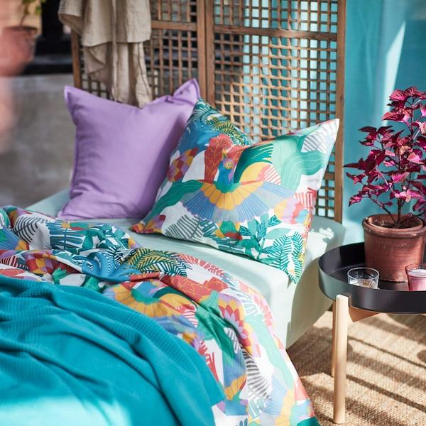 Een bed met een SKOGSFIBBLA dekbedovertrek en kussensloop, een INDIRA bedsprei en een lichtpaars kussen staat in een slaapkamer.