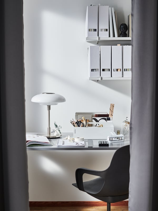 A chair and desk with a small table lamp and a desk organizer, below two shelves holding filled magazine holders.