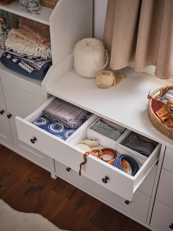 En hvid opbevaringsløsning med en åben skuffe med opbevaringskasser af tekstil med tekstiler, der er lagt pænt sammen.