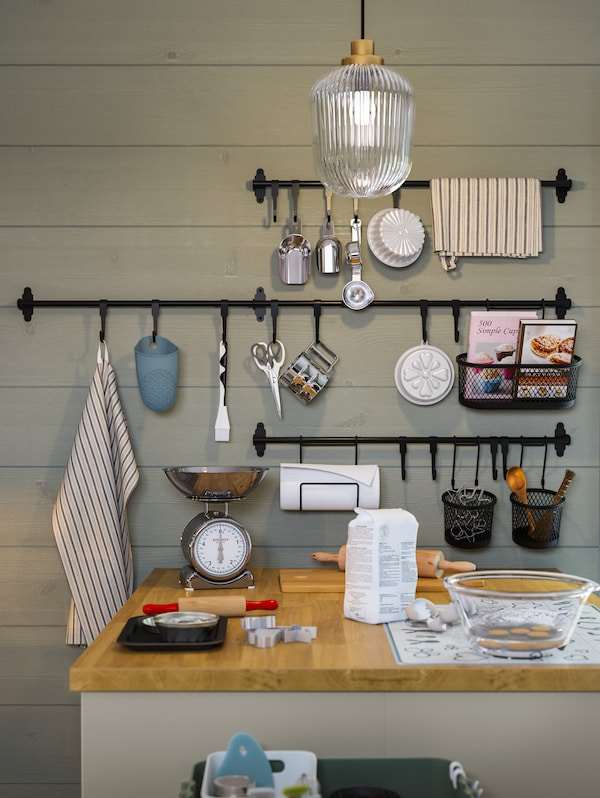 A kitchen island with bakeware, black rails and hooks with baking tools hanging on them against a green wooden wall.